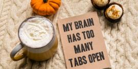 """Coffee with a book next to it that says """"My Brain Has Too Many Tabs Open."""""""